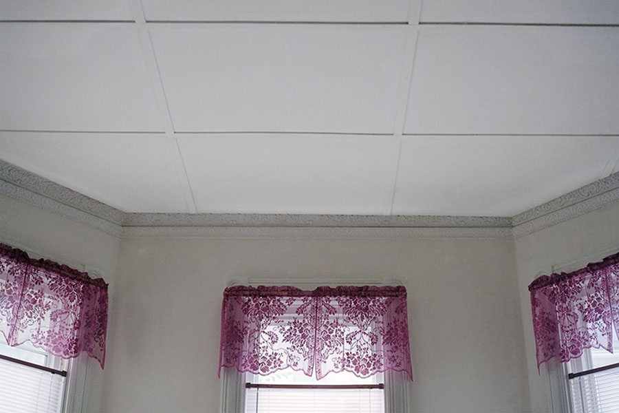 Digital Chromogenic Print. Color photograph, home interior, white ceiling tiles, octogon room, three windows, pink curtains, flower pattern