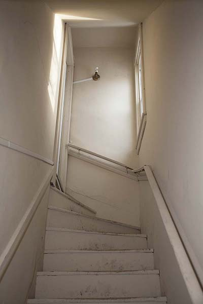 "20"" x 30"" Archival Inkjet Print. Color photograph. Claustrophobic stairway, beige interior, one window and door, light reflecting, dirty"