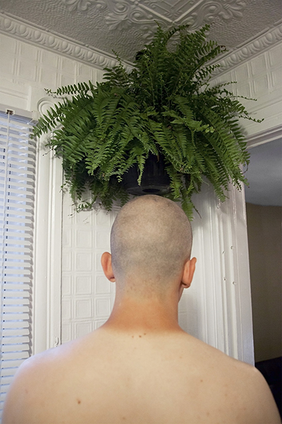 "20"" x 30"" Archival Inkjet Print. Color photograph. Back of a young man's head, shaved, tan line, fern, plant, corner of a room"